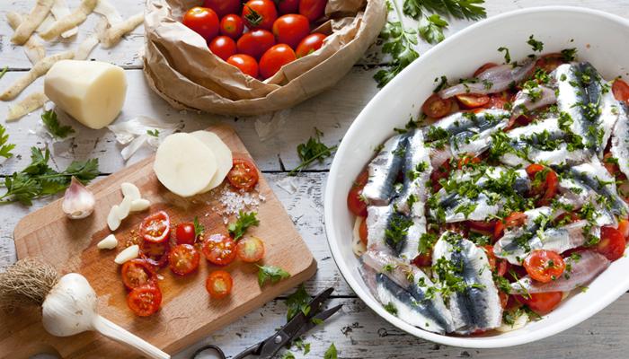Ricetta delle sarde al forno con patate alla curcuma e pomodorini